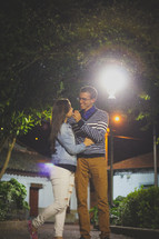 couple standing under a street lamp at night