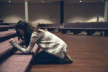 A woman kneeling in prayer