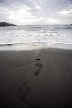 Footprints in the sand leading to the water