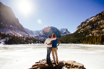 a couple hugging in front of a frozen lake