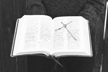 a woman holding a Bible and a cross made of sticks