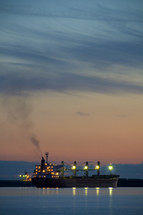 Lighted ship in the ocean at dusk.