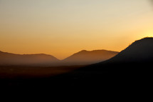 Distant hills with sunrise sky and misty mountains