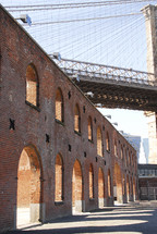 side of brick building with arches - under bridge