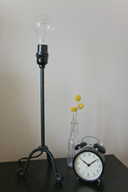 a lamp and alarm clock on a night stand