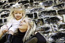 mother holding daughter on shoulders against stone wall