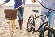 man and woman pushing beach cruiser bicycles on the beach