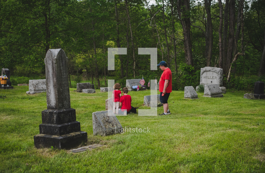 children visiting a cemetery with their father