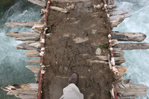 walking bridge made of mud and sticks over water