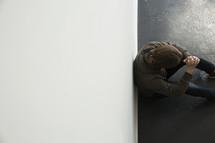man sitting against a wall praying