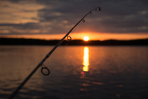 fishing pole over water at sunset