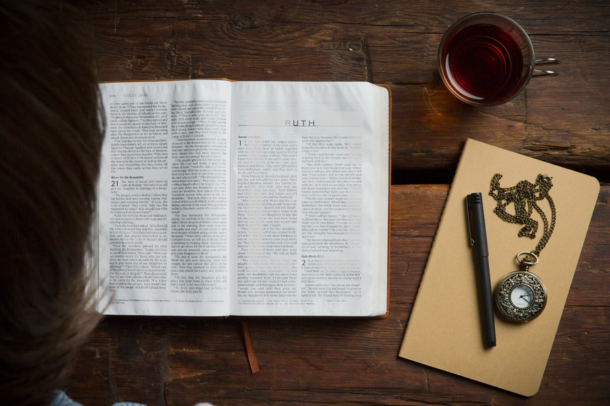 Reading the Bible on a wooden table.