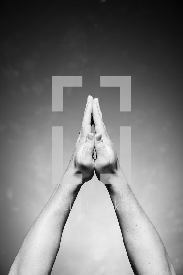 praying hands raised to the Lord