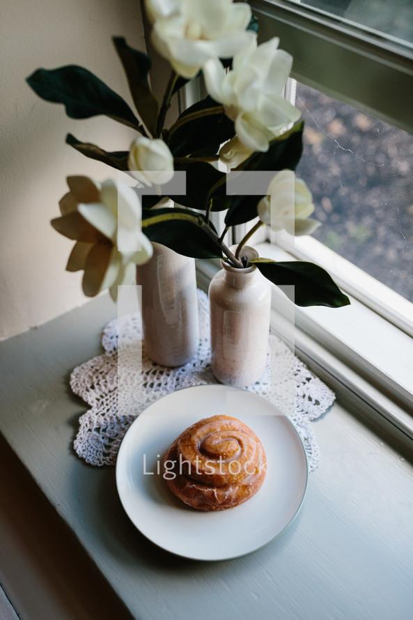 cinnamon bun on a plate on a table by a window