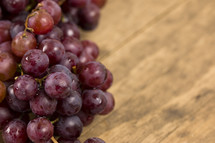 A cluster of grapes on a wooden table with room to write your own text