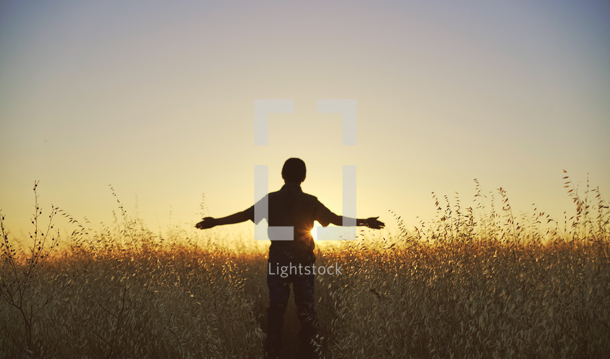 a young man with outstretched arms walking through a field of tall grass at sunset