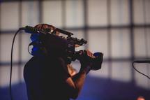man filming a concert