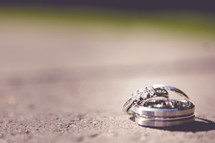 engagement ring and wedding band on concrete