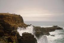 ocean water crashing into rock cliffs along a shore