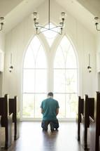 a man kneeling in prayer at church