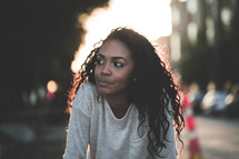 a young African-American woman outdoors under intense sunlight