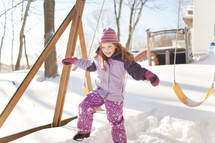 kids playing on a swing set in the snow