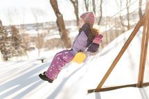 children on a backyard swing set in snow