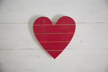 A red wooden heart on a white wood background.