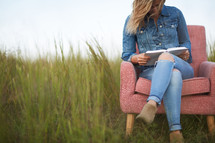 a woman sitting outdoors reading a Bible in a chair in a field of tall grass