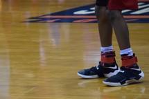 feet of a boy on a basketball court