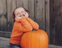 smiling child on an orange pumpkin