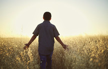 a young man walking through a field of tall grasses at sunset