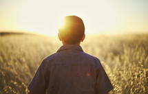a young man walking through a field of tall grass at sunset