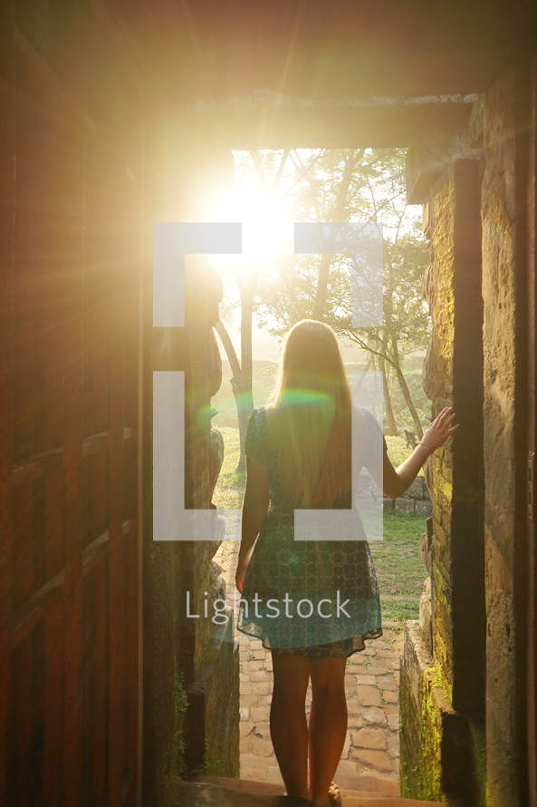 a woman standing in sunlight at the entrance of a door