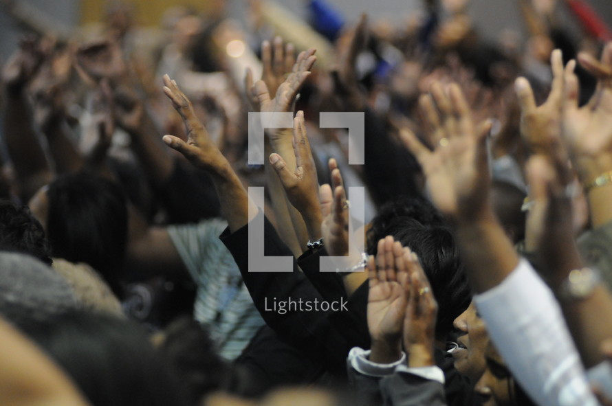 Congregation with hands raised praising God during worship service.
