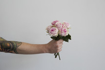 tattooed arm holding out flowers