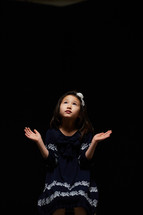 a girl with arms raised to praise the Lord