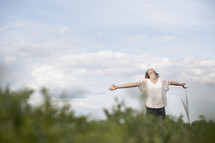 Woman outdoors with arms extended looking up to the heavens.