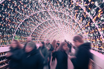 blurry image of people gathered to view Christmas lights