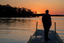 man standing on a dock at sunset