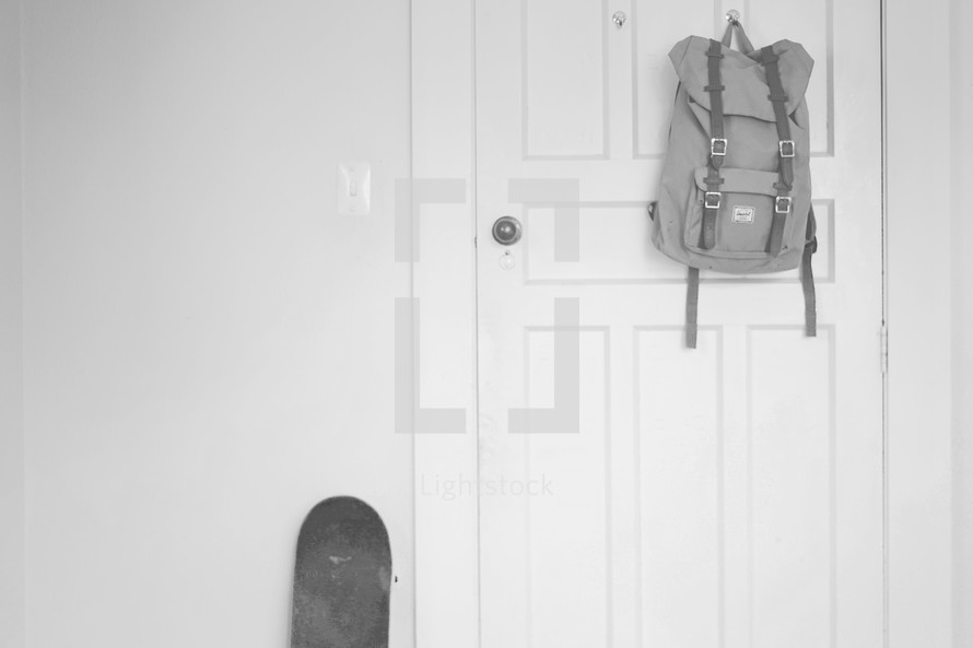 a book bag hanging on a door and a skateboard