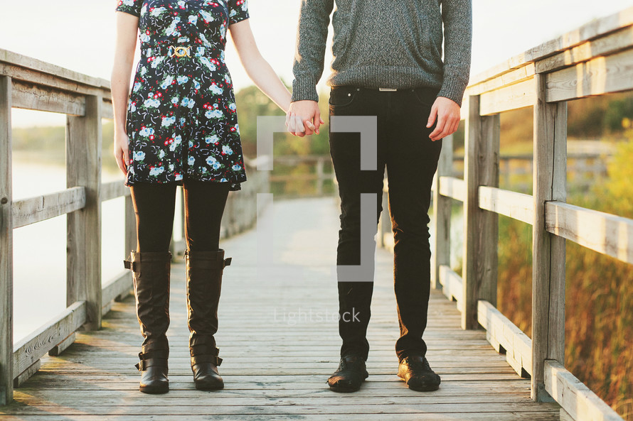 a couple standing on a bridge holding hands