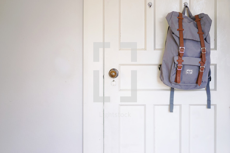 book bag hanging on the back of a door