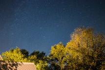 stars in the night sky over a house
