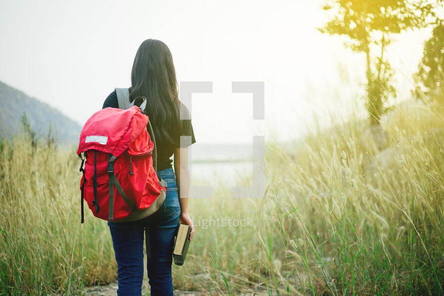 girl hiking carrying a Bible