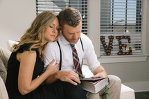 couple reading a Bible together and praying