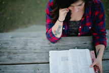 A woman reading a Bible outdoors.