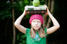 girl child holding a stack of books and an apple on her head