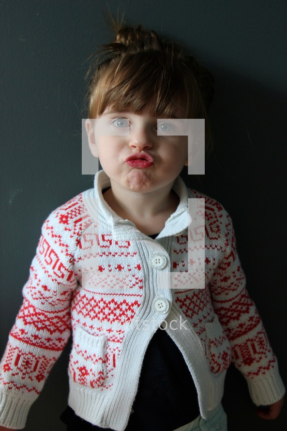 toddler girl standing in front of a chalkboard making a silly face