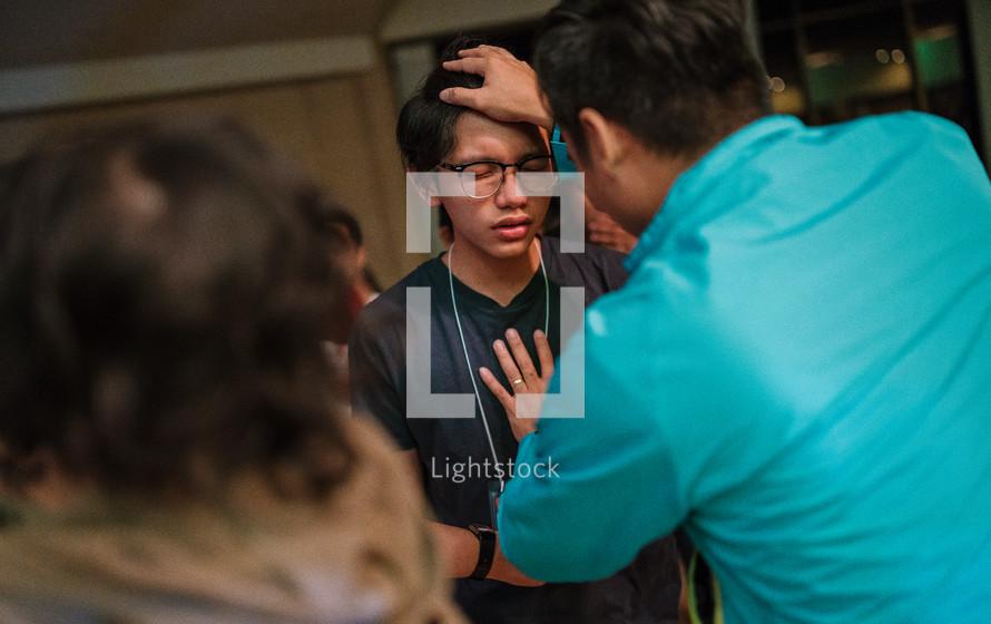 a teen boy receiving a blessing